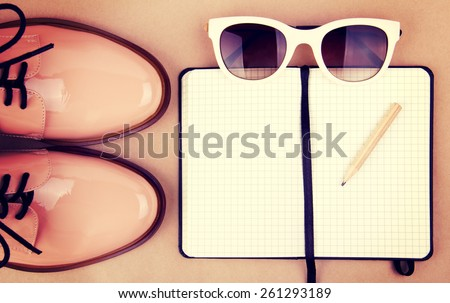 Shiny beige shoes on low heels, white sunglasses, wooden pencil and small black paper notebook. Vintage style edition. - stock photo