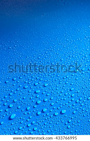 Shiny blue smooth surface covered with dew drops and lit from one side