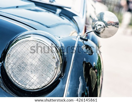 Shiny blue vintage car. Detail view of the headlight. Retro car. Front light. Retro automobile scene. Circle headlamp. - stock photo
