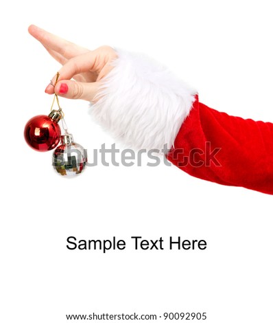 Shiny christmas baubles and girl hand dressed in santa claus costume on white background.Space for sample text on the bottom. - stock photo