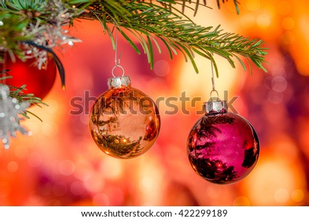 Shiny Christmas baubles hanging on a branch on a pine tree - stock photo