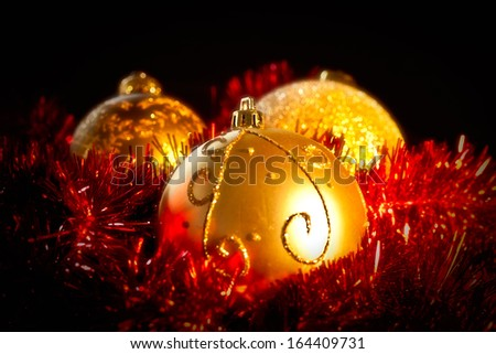 Shiny Christmas decorations against a black background - stock photo