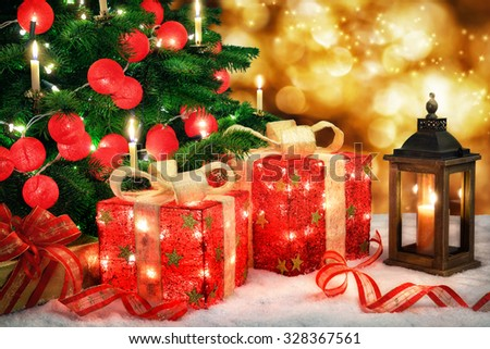 Shiny Christmas scene with a Christmas tree and illuminated red baubles, ornamental gift boxes with lamps, a lantern and bokeh lights background - stock photo