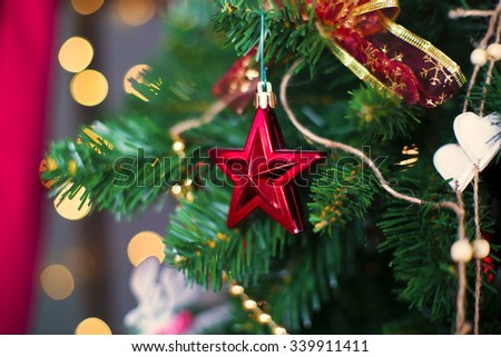 Shiny Christmas star hanging on pine branches with festive background - stock photo