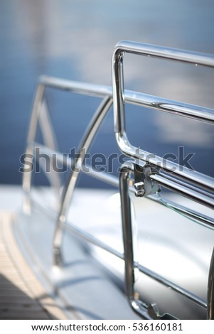 Shiny chrome metal fencing and railings yacht on the background of the smooth surface of the water