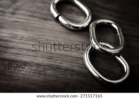 Shiny Chrome or silver chain links on a grungy wooden table. shallow depth of field. - stock photo