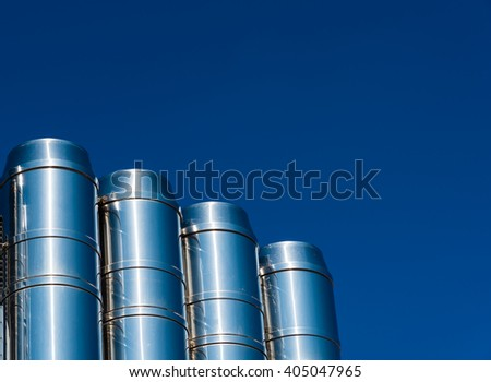 shiny chrome pipes agains the blue sky - stock photo