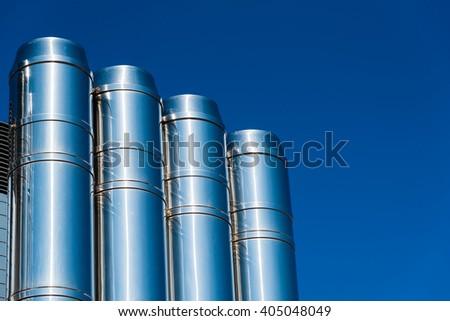 shiny chrome pipes against the blue sky - stock photo