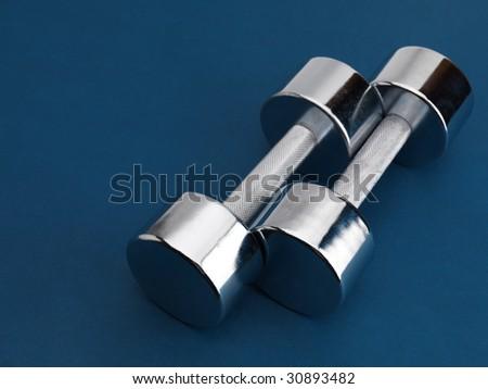 Shiny chrome plated fitness dumbbells isolated on blue background - stock photo