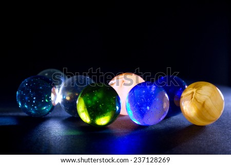 Shiny Colorful Translucent Glass Balls Against Black Background - stock photo