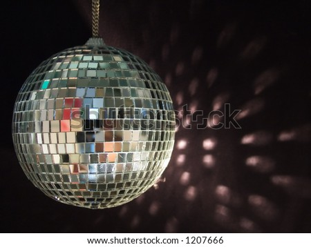 shiny disco ball with reflections on black background - stock photo