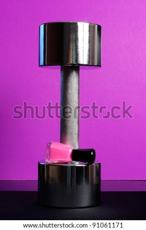 Shiny Dumbbell with Pink Nail Polish on Purple Background - stock photo