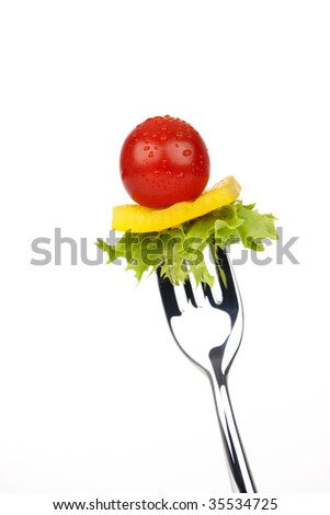 Shiny fork with red tomato, yellow bell pepper and green salad leaf - stock photo