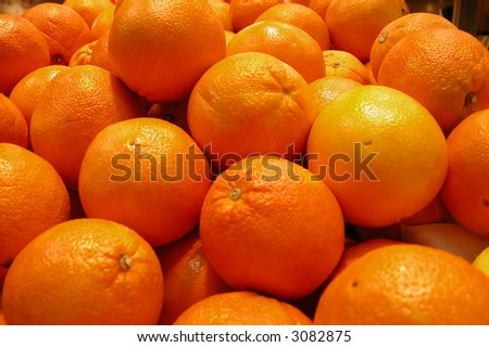 Shiny fresh oranges in a bin at a farmer's market - stock photo