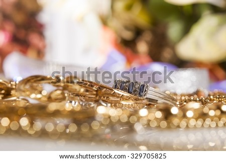 shiny gold and silver jewelery on white table - stock photo