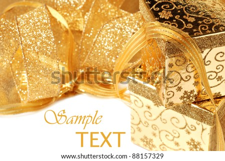 Shiny gold gift boxes and ribbon on white background with copy space.  Macro with shallow dof.  Selective focus on corner of top box. - stock photo
