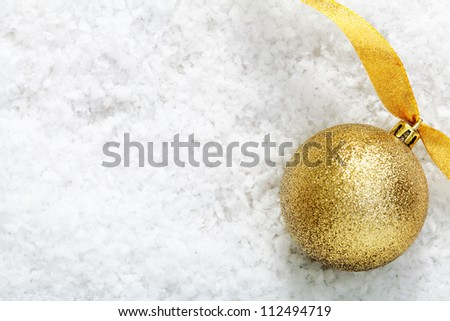 Shiny gold glitter bauble with a twirled golden ribbon on winter snow with copyspace for your Christmas message - stock photo