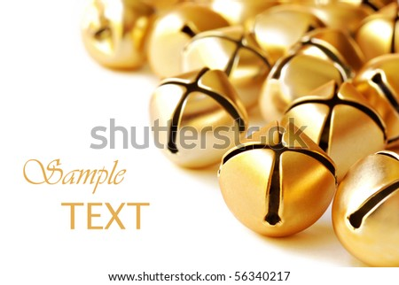 Shiny gold jingle bells on white background with copy space.  Macro with shallow dof. - stock photo
