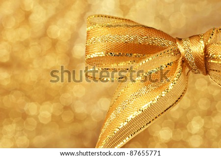 Shiny gold metallic bow against background of shimmery gold fabric (defocused) with copy space. - stock photo