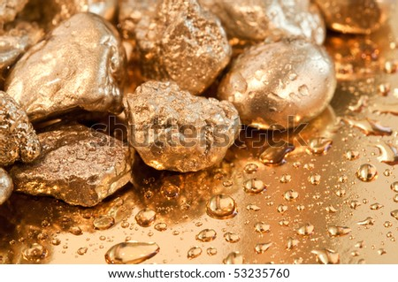 shiny gold nuggets and water drop background. closeup. - stock photo