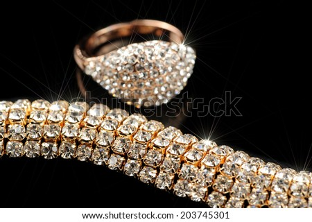 Shiny Gold Ring and Necklace on Black Background - stock photo