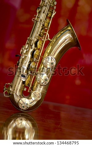Shiny golden shimmering saxophone on polished wooden floor, isolated with red background and optical reflection. - stock photo