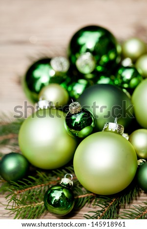 shiny green christmas baubles closeup macro and tree on wooden background