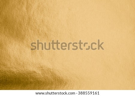 Shiny hot yellow gold foil leaf paper decorative texture background: Crumpled bright brilliant festive glossy metallic look textured backdrop: Aluminium tin metal steel material for design decoration - stock photo