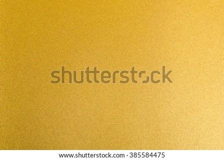 Shiny hot yellow gold golden brass decorative texture paper: Bright brilliant festive glossy metallic look textured empty wallpaper backdrop: Aluminium tin metal material for craft design decoration - stock photo