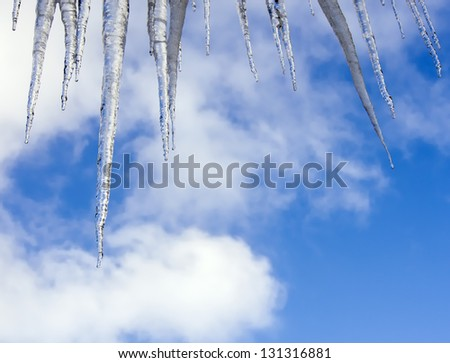 shiny icicles against blue winter sky - stock photo