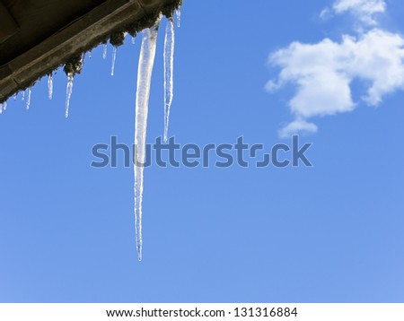 shiny icicles hanging down from a roof against a winter blue sky