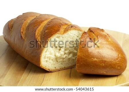 Shiny long bread sliced over wooden desk background - stock photo