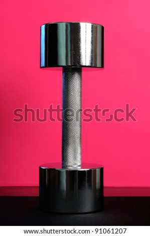 Shiny Metal Dumbbell on Pink Background - stock photo