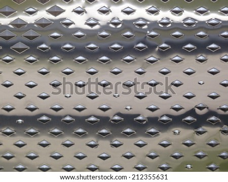 Shiny metal surface with diamond-shaped embossing.