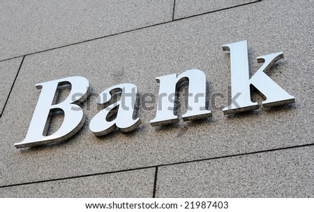 Shiny metallic bank sign on stone wall