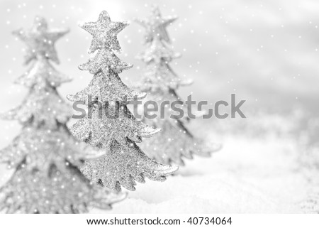 Shiny miniature tree ornaments on silver background with snow. High key black and white macro with extremely shallow dof.  Copy space included.
