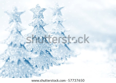 Shiny miniature tree ornaments on silver background with snow. High key blue toned macro with extremely shallow dof.  Copy space included. - stock photo