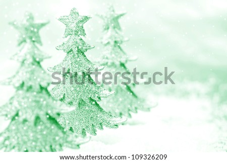 Shiny miniature tree ornaments on silver background with snow. High key, green toned macro with extremely shallow dof.  Selective focus on second tree.  Copy space included. - stock photo