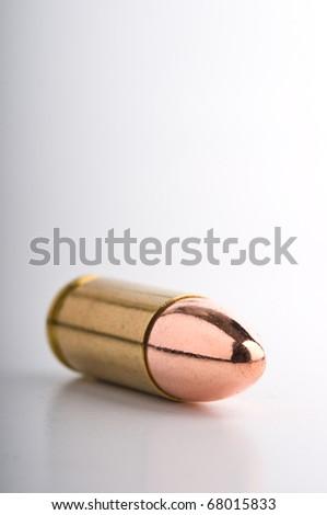 Shiny mm pistol cartridge on its shadow - stock photo