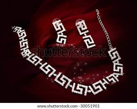 shiny necklace and earrings at red fabric - stock photo