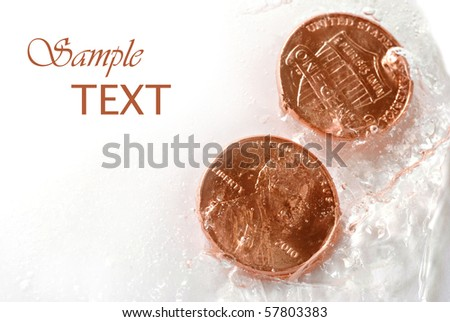 Shiny new pennies frozen in ice with copy space.  Financial concepts -  'frozen assets' , 'budget freeze', or 'cold hard cash' - stock photo