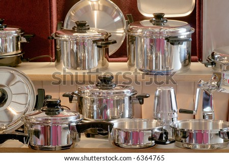 Shiny new pots and pans on a sellers shelf - stock photo