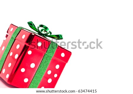 Shiny polka dot red and green Christmas present set on an angle with copy space