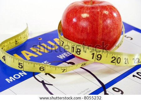 Shiny red apple with tailor's measure on a calendar with January 1st circled. - stock photo