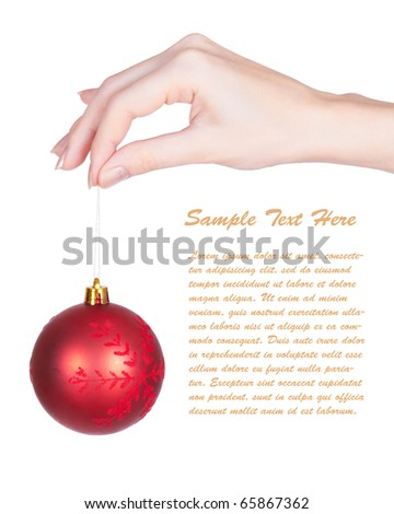 Shiny red christmas tree ball  and girls hand on white background with copy space. Closeup with shallow dof. - stock photo