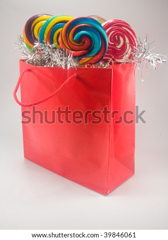 Shiny red gift bag filled with candy against plain background - stock photo