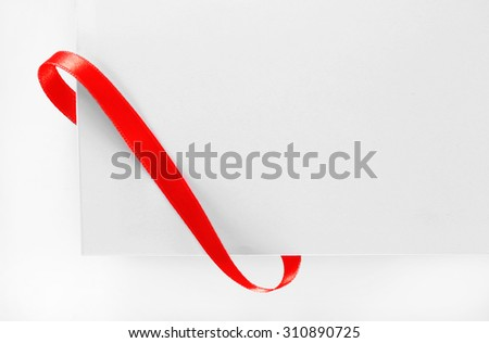 Shiny red ribbon with card close up - stock photo