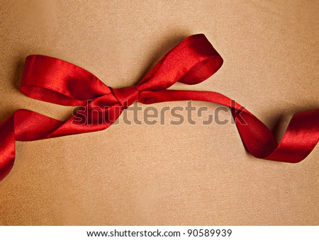 Shiny red satin ribbon on golden background with copy space - stock photo