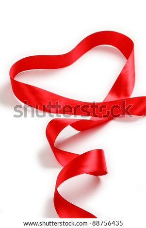 Shiny red satin ribbon with heart shape on white background with copy space. Macro with extremely shallow dof. - stock photo