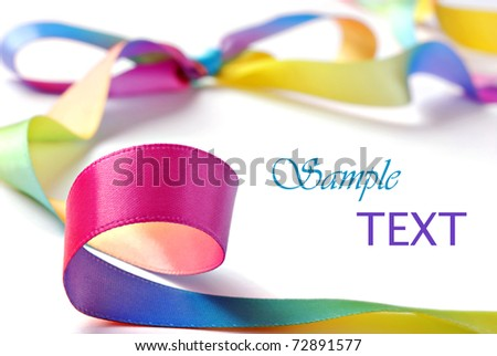 Shiny satin rainbow ribbon on white background with copy space.  Macro with extremely shallow dof. - stock photo